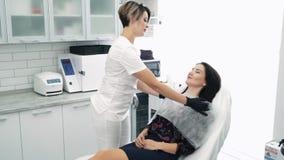 Femme à la réception à l'esthéticien, mouvement lent Le Cosmetologist prépare le patient pour la procédure cosmétique banque de vidéos