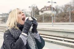 Femme à la station de train ayant un rhume Photographie stock