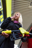 Femme à la station service à réapprovisionner en combustible Photographie stock