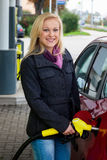 Femme à la station service à réapprovisionner en combustible Images libres de droits
