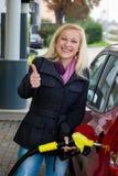 Femme à la station service à réapprovisionner en combustible Image stock