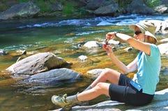 Femme à un fleuve prenant la photo Photographie stock libre de droits