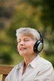 Femme âgée écoutant de la musique Image stock