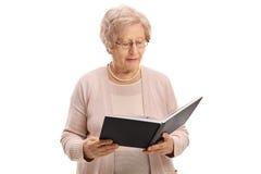 Femme âgée affichant un livre Photos libres de droits