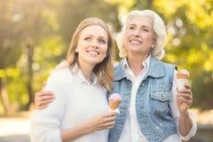 Femme âgée appréciant la crème glacée avec la fille dehors Photographie stock