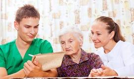 Femme âgée avec les jeunes médecins Images stock