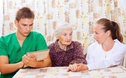 Femme âgée avec les jeunes médecins Image stock