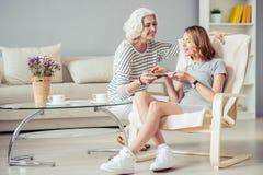 Femme âgée avec plaisir donnant à sa fille par morceau de tarte Photos stock