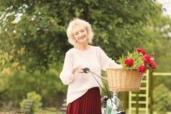 Femme âgée beau par milieu avec la bicyclette Photographie stock libre de droits