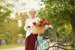 Femme âgée beau par milieu avec la bicyclette Images stock