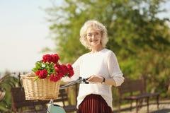 Femme âgée beau par milieu avec la bicyclette Photo stock