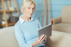 Femme âgée curieuse s'asseyant sur un sofa et tenant un comprimé moderne Photos stock
