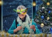 Femme âgée dans le masque de plume grillant un Joyeux Noël Photographie stock libre de droits