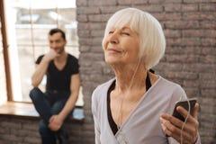 Femme âgée de sourire appréciant la musique pendant la classe de danse Photo stock