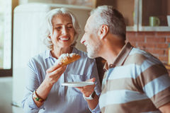 Femme âgée gaie donnant le croissant à son mari Photos stock