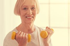 Femme âgée gaie tenant des haltères à la maison Photographie stock