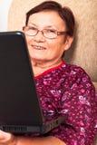 Femme âgée heureuse avec l'ordinateur portable Photographie stock