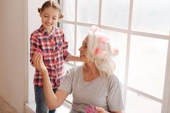 Femme âgée heureuse donnant un rouleau de cheveux à sa petite-fille Photographie stock