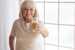 Femme âgée heureuse t'offrant un verre de jus Photo stock