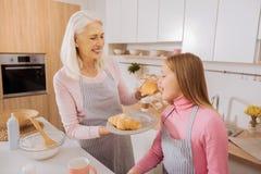 Femme âgée heureuse tenant un croissant Photographie stock
