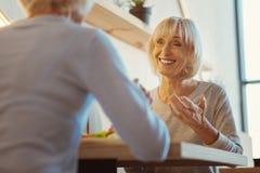 Femme âgée joyeuse ayant une conversation agréable Photographie stock