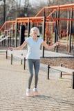 Femme âgée joyeuse sautant sa corde Photo libre de droits