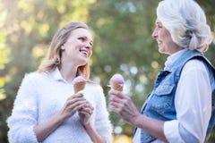 Femme âgée mangeant la crème glacée avec la fille mûre dehors Photo libre de droits