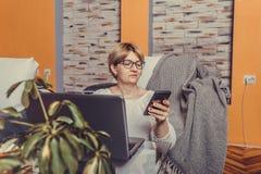Femme âgée moyenne à l'aide du smartphone et travaillant sur l'ordinateur portable à la maison photographie stock libre de droits