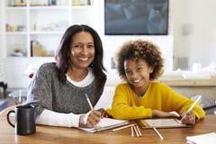 Femme âgée moyenne d'Afro-américain s'asseyant à la table dans son dessin de salle à manger avec sa petite-fille de la préadolesc photographie stock libre de droits