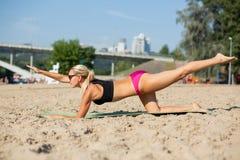 Femme âgée moyenne de forme physique dans des trains de maillot de bain sur la plage photographie stock