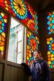Femme âgée moyenne regardant dans toute la fenêtre avec le verre souillé multicolore, vieux Tbilisi, la Géorgie, janvier 2019 images libres de droits