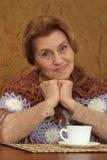 Femme âgée par chance s'asseyant sur un sofa Photo libre de droits