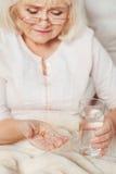 Femme âgée par malade prenant des pilules Photo libre de droits