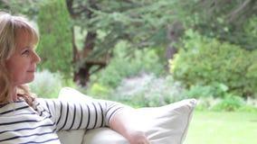 Femme âgée par milieu attrayant s'asseyant dehors et souriant banque de vidéos