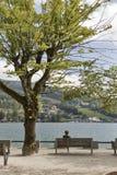 Femme âgée par milieu blanc s'asseyant sur le banc Lac Mondsee, Autriche Images stock