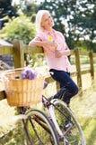 Femme âgée par milieu détendant sur le tour de cycle de pays Image libre de droits