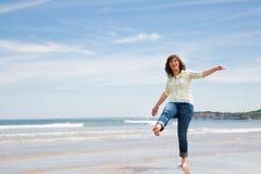 Femme âgée par milieu espiègle sur la plage image libre de droits