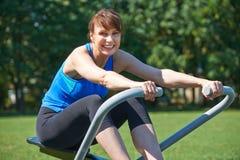 Femme âgée par milieu Exercicing sur la machine à ramer en parc images stock