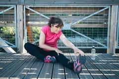 Femme âgée par milieu faisant étirant des exercices photos stock