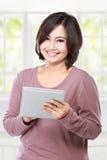 Femme âgée par milieu occasionnel tenant la tablette Photos stock
