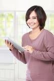 Femme âgée par milieu occasionnel tenant la tablette Image stock