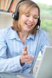 Femme âgée par milieu parlant en ligne utilisant le casque images libres de droits