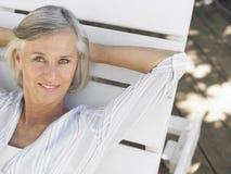 Femme âgée par milieu reposant sur la chaise longue Photographie stock