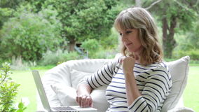 Femme âgée par milieu s'asseyant dehors utilisant l'ordinateur portable banque de vidéos