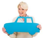 Femme âgée par milieu tenant le symbole de voiture Photos libres de droits