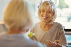 Femme âgée par positif parlant à son ami Image stock