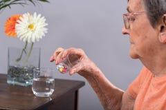 Femme âgée prenant le médicament Images libres de droits