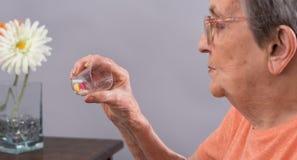 Femme âgée prenant le médicament Photographie stock