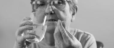 Femme âgée prenant le médicament Image libre de droits