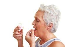 Femme âgée prenant une pillule Photographie stock libre de droits